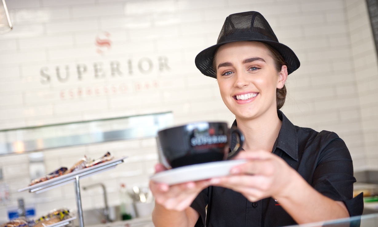 Smiling female catering assistant serving coffee